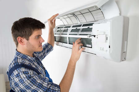 Photo Of Young Male Technician Repairing Air Conditioner Archivio Fotografico