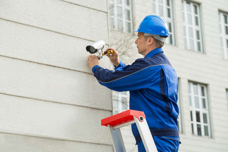 technician: Mature Male Technician Installing Camera On Wall With Screwdriver
