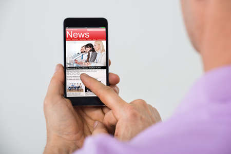 articles: Close-up Of Mature Man Reading News On Smartphone Stock Photo