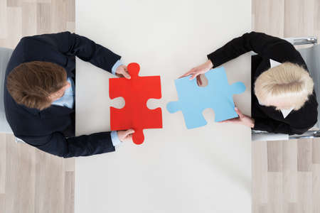 two piece: High Angle View Of Two Businesspeople Connecting Puzzle Pieces At Office Desk