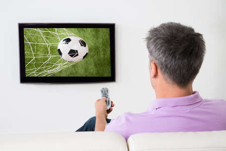 mature man: Man Watching Soccer Game On Television At Home Stock Photo