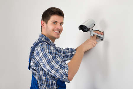 setup man: Close-up Of Technician Adjusting CCTV Camera On Wall