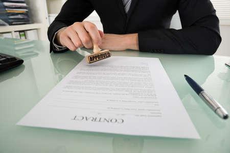 sello: Primer plano del hombre de negocios de la mano de sellar autorizada en el papel del contrato