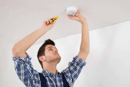 technician: Male Electrician With Screwdriver Repairing Fire Sensor