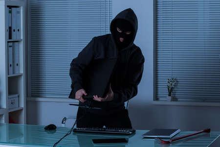 사무실에서 밤에 컴퓨터를 훔치는 도둑 스톡 콘텐츠