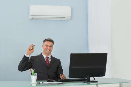 air: Mature Happy Businessman Sitting On Chair Using Air Conditioner In Office