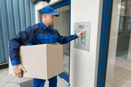 intercom: Delivery Man With Cardboard Box Pressing Button Of Intercom To Enter Building