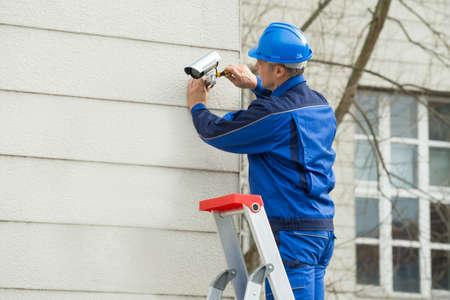 setup man: Mature Male Technician Standing On Stepladder Fitting CCTV Camera On Wall Stock Photo