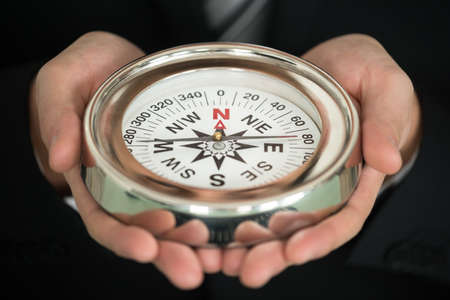 guiding: Close-up Photo Of Businessman Hand Holding Compass
