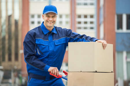 deliveryman: Mature Happy Deliveryman With Trolley Loaded With Cardboard Boxes Standing On Street