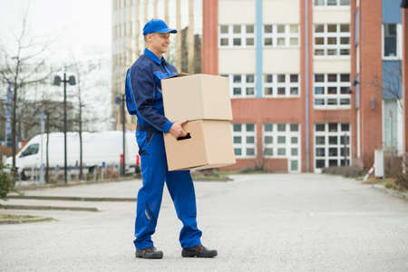 man carrying box: Mature Happy Delivery Man Carrying Cardboard Box Stock Photo