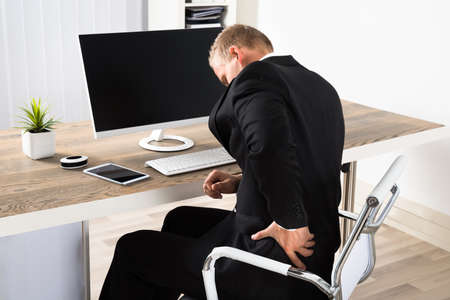 backpain: Young Businessman Suffering From Backpain While Working In Office