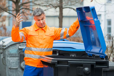 recolector de basura: Unhappy Male Street Cleaner Looking In Dustbin