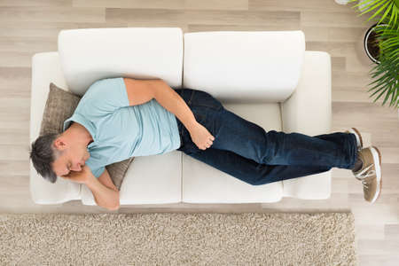 couch: Portrait Of A Man Sleeping On Couch At Home Stock Photo