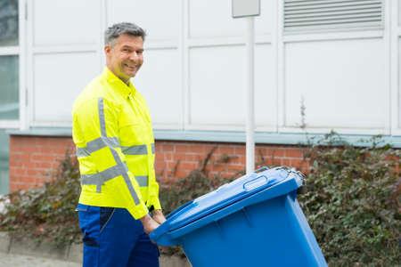 recolector de basura: Trabajador de sexo masculino feliz que recorre con los Cubo de basura en la calle durante el día