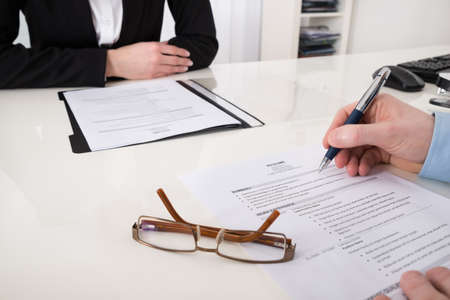 resume: Close-up Of Businessperson With Resume And Pen In Office Stock Photo