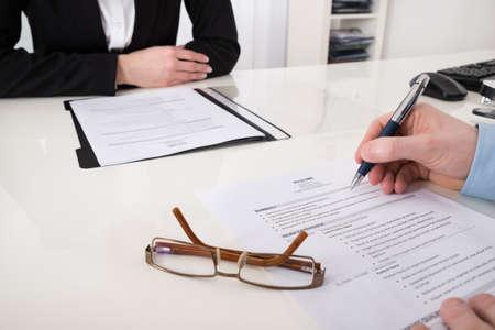 Close-up Van Ondernemer Met Resume En Pen In Office