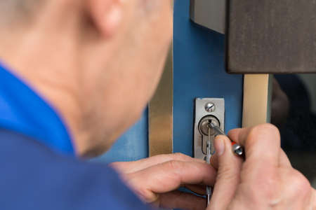 Close-up Of Male Lockpicker Hand Fixing Door Handle At Home