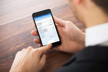 deposit: Close-up Of Businessman Doing Online Banking On Mobilephone At Office Desk Stock Photo