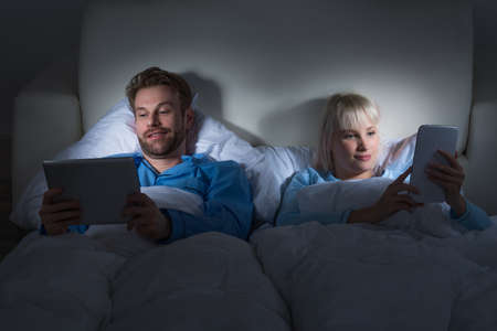 bedcover: Young Happy Couple Lying In Bed Using Digital Tablets
