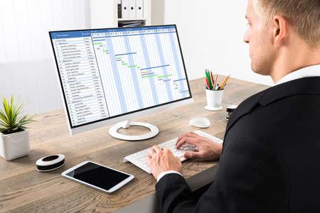 El hombre de negocios joven que trabaja en diagrama de Gantt El ordenador en la oficina