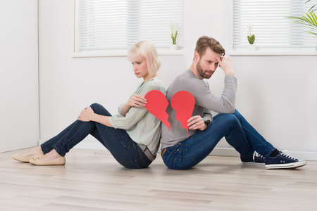 broken back: Sad Couple Sitting Back To Back Holding Red Broken Heart Stock Photo