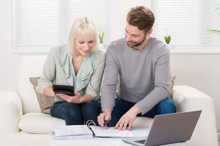 taxes budgeting: Young Happy Couple Sitting On Sofa Calculating Budget