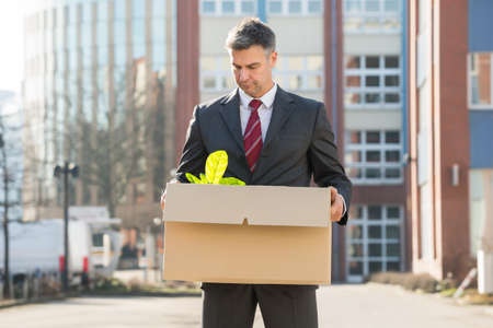 layoff: Disappointed Businessman Standing With Cardboard Box Outside Office Stock Photo