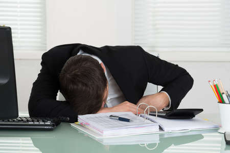 INVOICE: Young Businessman Sleeping With Invoices On Desk In Office