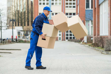 Delivery Man With Falling Stack Of Boxes On Street Stok Fotoğraf