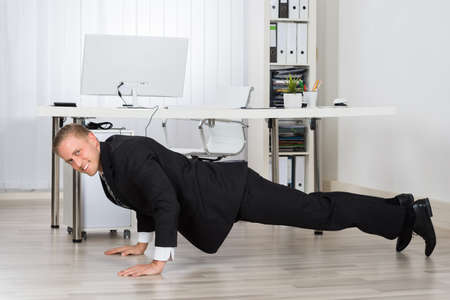 corporate office: Young Businessman Doing Pushup At Work In Office