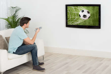 watching football: Young Man Sitting On Sofa Watching Football Match On Television Stock Photo