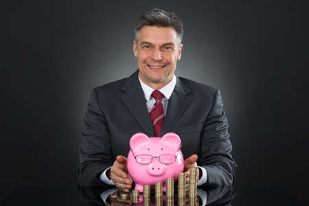 sheltering: Mature Happy Businessman Sheltering Coins And Piggybank At Desk Stock Photo
