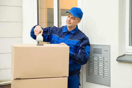 barcode scanner: Mature Delivery Man Scanning Cardboard Boxes With Barcode Scanner