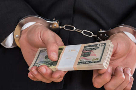 deceit: Close-up Of Businessman In Handcuffs Holding Dollars For Bribe Stock Photo