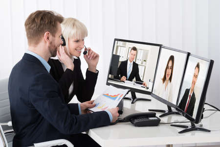 conferencing: Two Businesspeople Video Conferencing On Desk With Multiple Computer