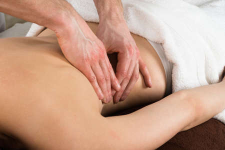 massage table: Close-up Of A Young Woman Getting Back Massage From A Massager In A Beauty Spa