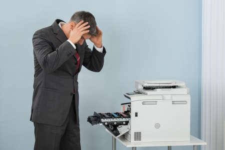 Irritated Mature Businessman Looking At Printer Machine At Office Stock fotó