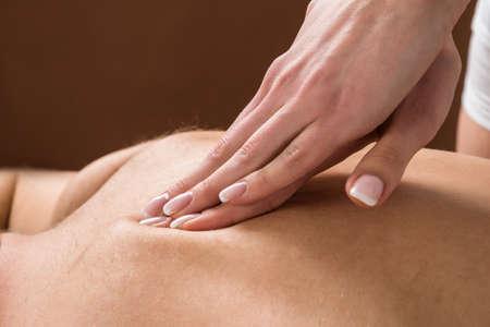 masaje deportivo: Primer plano del hombre joven que recibe el masaje posterior en un balneario de la belleza Foto de archivo