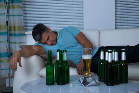 african man: Man Taking A Nap On Sofa In Front Of Beer Bottles During Night Stock Photo