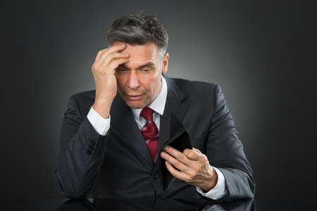Sad Businessman With Empty Wallet Sitting At Desk Against Gray Background