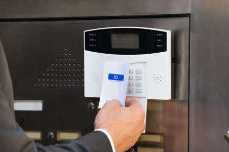 keycard: Close-up Of Businessperson Hands Inserting Keycard In Security System To Unlock Door