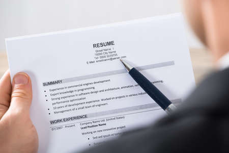 Close-up Of A Businessman Analyzing Resume At Desk In Office