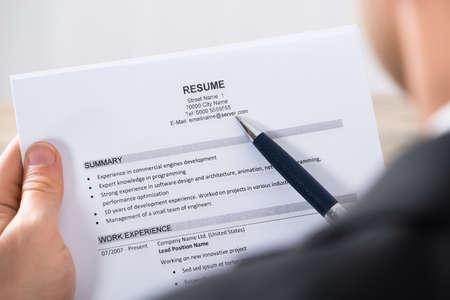 hoja de vida: Primer plano de un curriculum vitae Analizando empresario en el escritorio de oficina