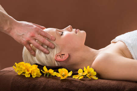 aroma facial: Young Woman Receiving Head Massage From A Massager At A Beauty Spa Stock Photo