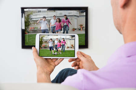 Closeup Of Man Holding Smartphone Connected To A TV Stock Photo