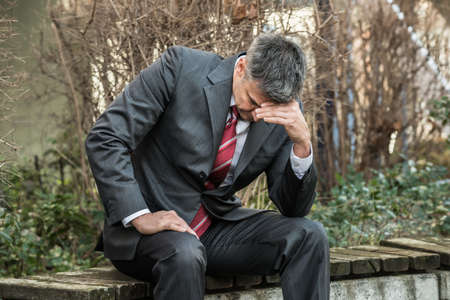 job loss: Sad Businessman Sitting On The Bench Outdoors And Having Headache