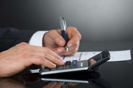 Close-up Of Businessman Using Calculator While Checking Invoice At Desk Against Gray Background