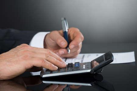 Close-up van de zakenman met Calculator tijdens het controleren van Invoice Bij Bureau tegen grijze achtergrond