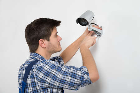 security equipment: Close-up Of Technician Adjusting CCTV Camera On Wall